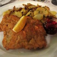 Dunajski zrezek s pečenim krompirjem in brusnično omako v pivnici Augustiner Keller v Münchnu